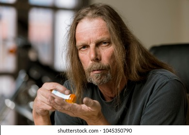 Man holding an opioid pill bottle
