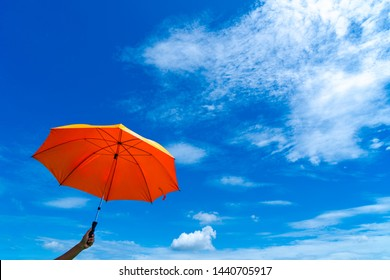 The man holding orange umbrella in bottom view for protect skin from the sun, high uv on the blue summer sky with white fluffy clound. Freedom in the blue sky.