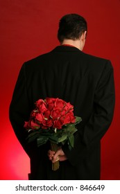 man holding out large bouquet of red roses behind his back on red backdrop