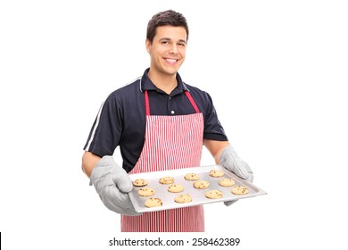 Man holding a pan full of chocolate chip cookies isolated on white background