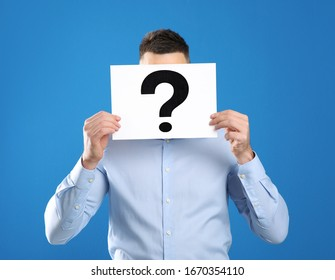 Man holding paper with question mark on blue background