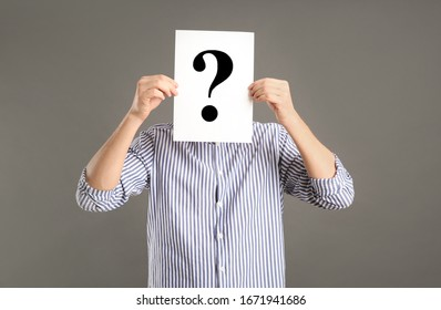 Man holding paper with question mark on grey background