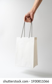 Man holding paper shopping bag on whie background