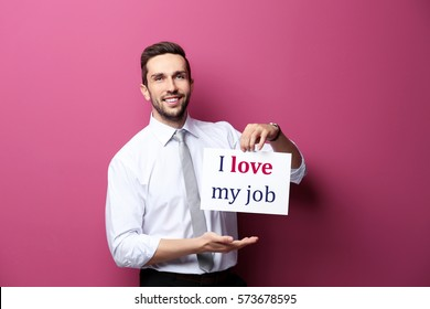 Man holding paper with text I LOVE MY JOB on color background