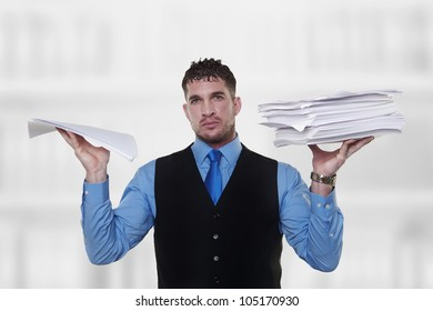 man holding a lot of paper work up in the air a pile in each hand