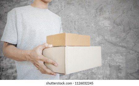 a man holding parcel boxes package, on concrete texture backgrounds