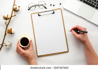 Man holding a pen and coffee. Home office workspace mockup with laptop, clipboard, notebook and accessories. Flat lay, top view. Template for blog, bloger