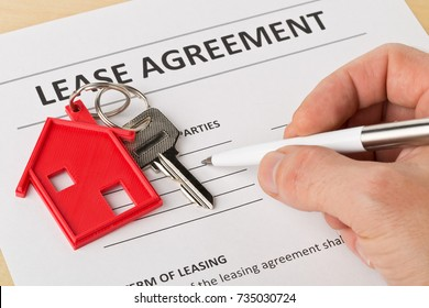 Man holding pen over house door key with red keychain pendant and lease agreement form on wooden desk - house or apartment rental concept