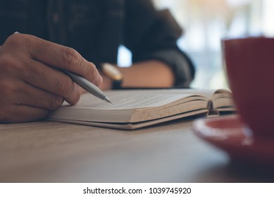 Man holding pen and reading book with cup of coffee on wooden desk