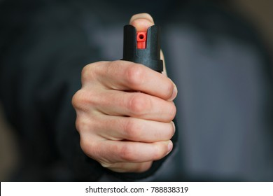 Man holding pepper spray (tear gas) in his hand. Self defense. Blur background, close up.