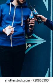 Man holding pepsi and hot-dog