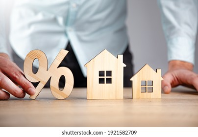 man holding percent with house models