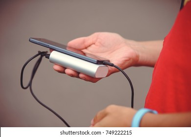 the man is holding the phone and the charger. Powerbank and smartphone in hand. Power-saving device power bank smartphone.