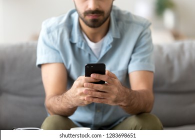 Man holding phone in hands texting message or using mobile apps, checking social media applications on new black smartphone, working playing game on cellphone, male customer and gadget close up view