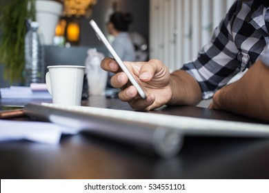 The man holding a phone at the table office
