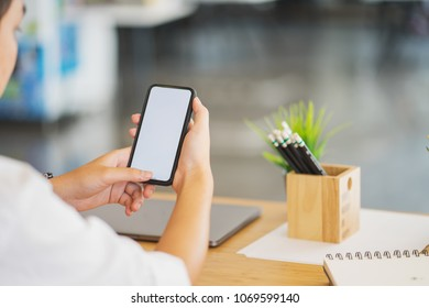 man holding a phone with white screen over the desk in the office