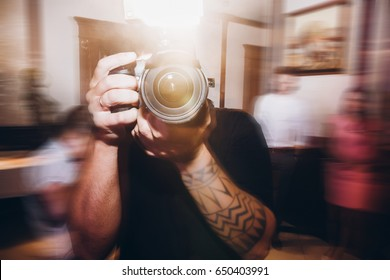 man holding photo camera, photographer at wedding ceremony reception,