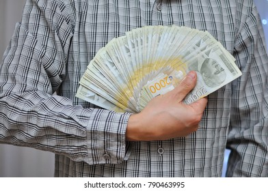 Man holding pile of money. Serbian dinar paper currency, 2000 dinars value. Business and success concept