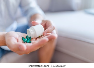 Man holding pills on hand. Medicine and health care concept. Hand spilling pills for the pain of a bottle in the living room. Healthy lifestyle, medicine, nutritional supplements and people concept