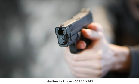 Man holding a pistol in a firing position. Personal defense concept