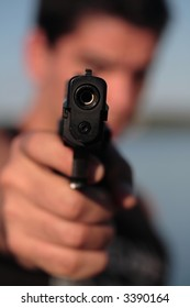 A man holding a pistol and pointing it at the camera. (This image is part of a series).