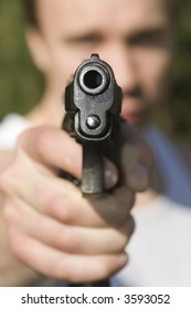 A man holding a pistol and pointing it at the camera.
