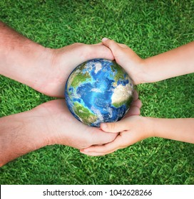 The man holding planet Earth with baby against green grass background. Ecology concept, earth day. Elements of this image furnished by NASA