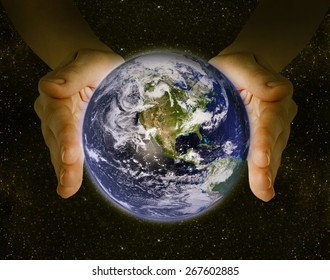 man holding the planet earth in the hands against the background of the galaxy. Elements of this image furnished by NASA