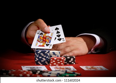 Man holding poker cards on red background