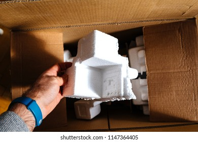 Man holding polystyrene packaging detail of a cardboard box during unboxing