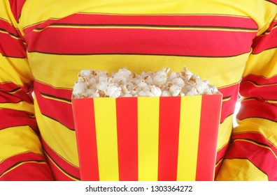 Man is holding popcorn in red and yellow stripes cardboard box for cinema or TV