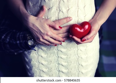 man holding pregnant women with heart shape