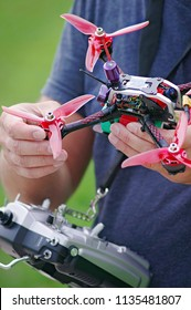 Man holding racing drone in hands, remote controller. Close-up view