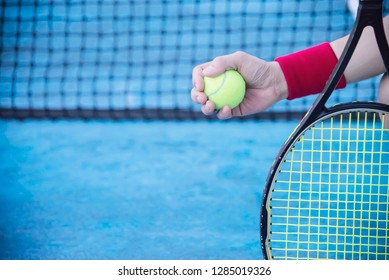 Man holding racket about to play a ball in tennis court - sport player tennis game concept