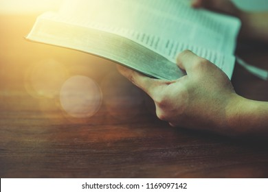 A man holding and read book on wood table with window and bokeh light, open bible with blurred page