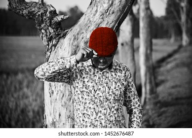 Man holding a red cap standing around a place unique photo