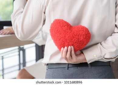 Man holding red heart behind his back to surprise woman, love and valentine concept
