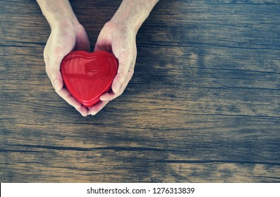 Man holding red Heart in hands for love Valentines day / Donate Help Give love warmth take care concept on wooden table rustic background