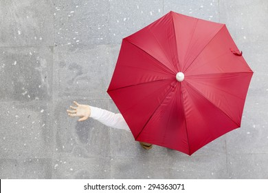 Man holding a red umbrella outdoors