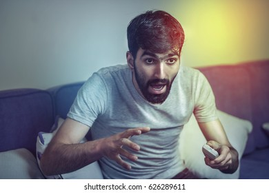 man holding remote control and looking surprised while watching TV sitting on the sofa