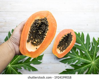 A man holding a ripe papaya fruit cut in half. With papaya leaves On a white tone wooden background