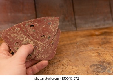 Man holding sandpaper in Hand for the renovation of the old wooden staircase