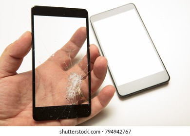 Man holding a shattered smartphone screen in his hand with the mobile phone visible below in a close up view showing the damage to the glass