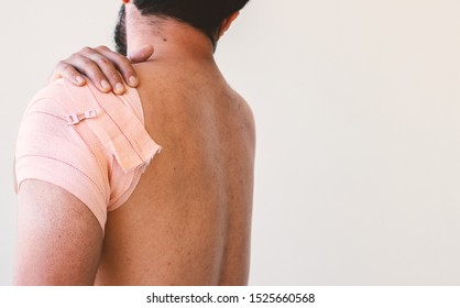 man holding shoulder bandage as feeling pain due to raptured muscle