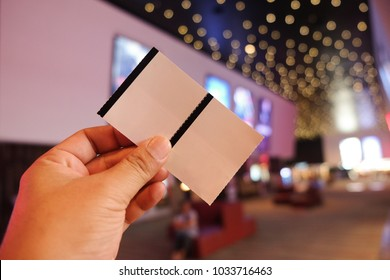 Man holding or showing two cinema tickets (Booking ticket concept)