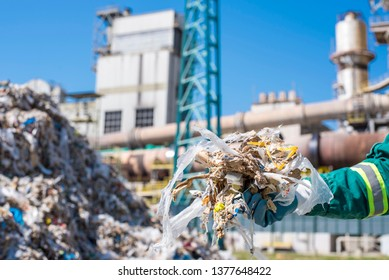 Man holding shredded municipal waste in front of rotary cement kiln used as alternative fuel