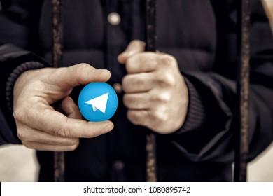 Man holding sign of blue coin depicting white airplane ICO Gram. Concept Telegram messenger is banned. Roskomnadzor blocked Telegram service