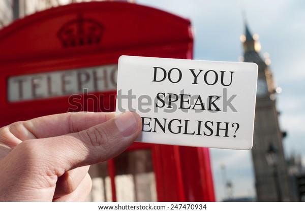 ¿Un hombre con un cartel con el texto habla inglés? con una cabina telefónica roja y el Big Ben al fondo, en Londres, Reino Unido