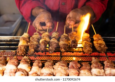 Man holding a skewer with meat grilling on fire.