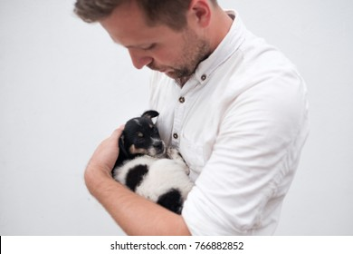 Man holding a small puppy in his hands. He has find new friend.